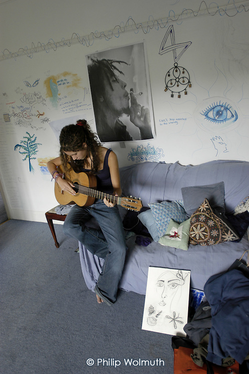 A teenage girl plays guitar in her bedroom, in front of a poster of Bob Marley smoking a spliff (posed by model).