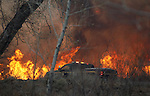 A Nevada Highway Patrol trooper drives past a fast-moving brush fire burns in Pleasant Valley, south of Reno, Nev., on Thursday, Jan. 19, 2012. (AP Photo/Cathleen Allison)