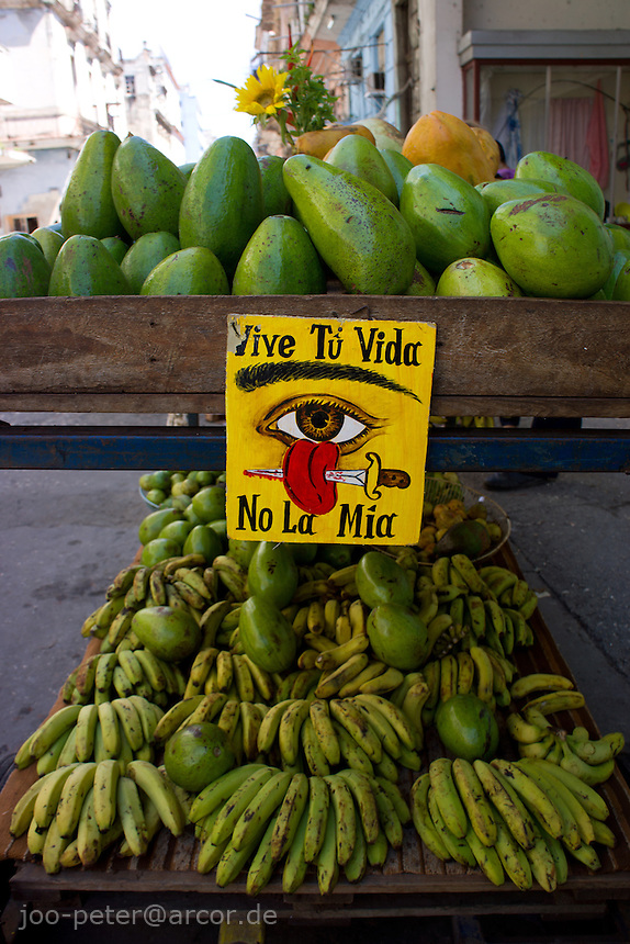 "a fruit seller in the streets of Havanna Centro protects his buisness by Santeria cult items like sun flowers and a sign saying ""Vive tu vida - no la mia"" - Live your live, not mine. The watching eye and a tongue thrilled by a dagger is believd to turn back lies,  bad talk, envy and evil spirit on everybody coming with bad intentions."