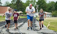 Jacob Gulbransen of Bella Vista starts the time as he takes off on a race Thursday, May 14, 2020, with his children Tate Gulbransen (from left), 12, Sawyer Gulbransen, 10, and Brightyn Gulbransen, 13, and their pet duck Smitty at Old Tiger Stadium Park in Bentonville. Deon Gulbransen, the mother of the family, said Smitty likes to line up at the start line, but doesn't like to run. Go to nwaonline.com/200515Daily/ to see more photos.<br /> (NWA Democrat-Gazette/Ben Goff)