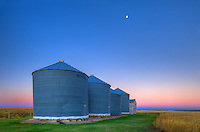 Grain bins at dawn with moon<br /> near Swift Current<br /> Saskatchewan<br /> Canada