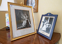 BNPS.co.uk (01202 558833)<br /> Pic: PhilYeomans/BNPS<br /> <br /> The house is full of Royal momento's, including these signed photograph's from the Queen.<br /> <br /> A remarkable 'timewarp' archive amassed by a dressmaker to the Queen has sold for over £100,000.<br /> <br /> The late Ian Thomas meticulously kept his fashion designs, letters, cards and photographs relating to the Queen at his home that was more like a museum. <br /> <br /> He helped design the Queen's coronation gown in 1953 as well as the powder blue outfit she wore for Charles and Diana's wedding in 1981.<br /> <br /> The lifelong bachelor passed away in 1993 and left his home and its contents to a florist he had been good friends with for 25 years.<br /> <br /> After she died in 2015 the property was inherited by a relative who also knew Mr Thomas well.<br /> <br /> She has now sold the contents at auction.