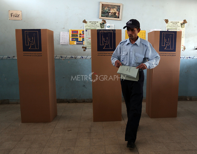 BAGHDAD, IRAQ: Policemen vote in in Baghdad...Three days before the polls open, military and convicts vote in the Iraqi Parliamentary Elections...Photo by Metrography