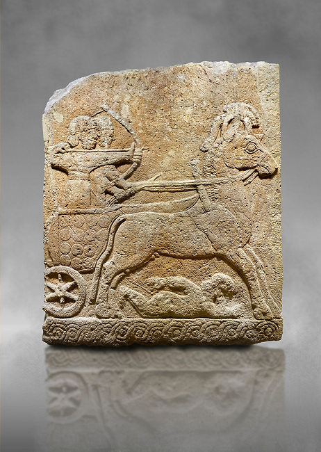 Hittite relief sculpted orthostat stone panel of Long Wall Limestone, Karkamıs, (Kargamıs), Carchemish (Karkemish), 900 - 700 B.C. Chariot. Anatolian Civilisations Museum, Ankara, Turkey<br /> <br /> One of the two figures in the chariot holds the horse's headstall while the other throws arrows. There is a naked enemy with an arrow in his hip lying face down under the horse's feet It is thought that this figure is depicted smaller than the other figures since it is an enemy soldier. The lower part of the orthostat is decorated with braiding motifs. <br /> <br /> On a grey art background.