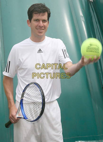 TIM HENMAN.Helped Slazenger launch their Wimbledon activity with a photocall at The Hanbour Club, Chelsea, England..May 12th, 2009.half length white t-shirt trousers tennis racket large big oversized ball .CAP/DS.©Dudley Smith/Capital Pictures