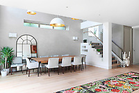 Pendant lights hang from a double height ceiling above a dining table and chairs for eight. The spacious room has a staircase with a stair lift facility.
