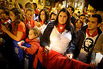 Revellers raise red scarves and candles as they sing the song 'Pobre de Mi', marking the end of the San Fermin festival in Pamplona early on July 15, 2012. The festival is a symbol of Spanish culture that attracts thousands of tourists to watch the bull runs despite heavy condemnation from animal rights groups . (c) Pedro ARMESTRE