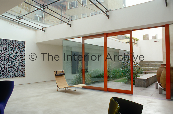 View from the living room on the ground floor out through sliding plate-glass windows to an inner courtyard