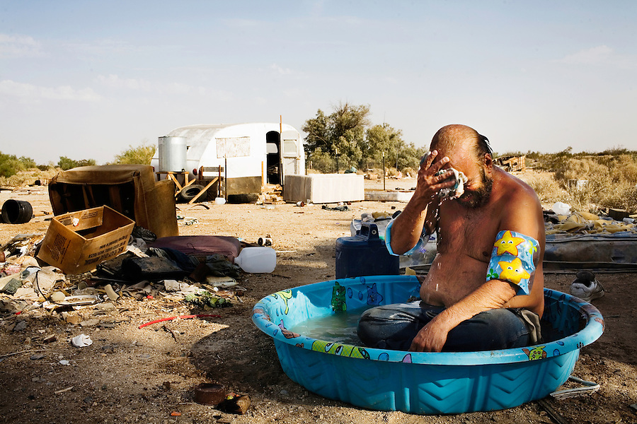 """Niland, California, August 2, 2008 - Borrowing the pool used by his six dogs to keep cool during the summer heat, Willie Reynolds, cools off with his weekly bath. He was given arm floaties for his birthday. He says, """"They are good to keep me from drowning."""" Adding, today is my birthday, so I wanted to take a bath for my party."""" Willie's friends threw him a barbecue and surprised him with a cake."""