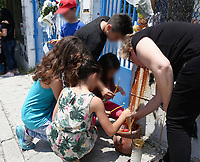 "Pictured: Locals leave flowers and tributes left at the gate of the 6th primary School in Acharnes, Athens, Greece. Saturday 10 June 2017<br /> Re: An 11 year old boy has been shot dead by a ""stray bullet"" during a school celebration in Acharnes (Menidi) area, in the outskirts of Athens, Greece.<br /> Marios Dimitrios Souloukos ""complained to his mum"" who works as a teacher at the 6th Primary School of Acharnes that he was feeling unwell, he then collapsed with blood pouring out from the top of his head.<br /> His mum tried to revive him assisted by other teachers while his schoolmates who were reportedly upset, were hurriedly removed by their parents.<br /> According to locals an ambulance arrived 25 minutes late.<br /> Hundreds of police officers have been deployed in the area and have raided many properties.<br /> Shells matching the fatal bullet which hit the boy on the top of his head were found in a house yard nearby.<br /> Local people reported hearing shots being fired at a nearby Romany Gypsy camp before the fatal incident.<br /> The area has been plagued with criminality during the last few years."