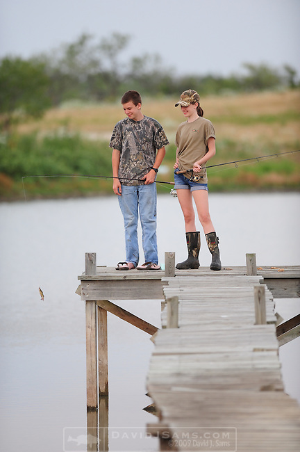 FISHING POND..Girl and Boy age 13-14 fish for bluegill and catfish on  farm pond near Waco Texas
