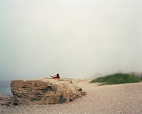 A woman does exercises on a misty beach in Aktau, overlooking thr Caspian Sea.