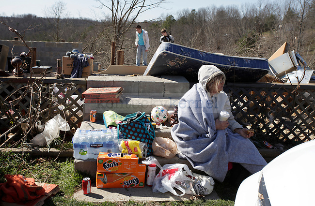 Carol Rhodes sits on the steps of what remains of her home in East Bernstadt, Ky. Her home was completely destroyed during the March 2 tornado that left five people in Laurel County dead. Residents were allowed back into the community on March 3, 2012 to collect belongings. Photo by Latara Appleby | Staff ..