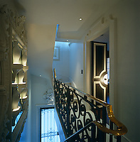 The staircase landing has an ornate metal balustrade and a display of white ceramic vases on the wall