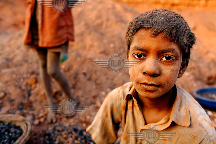A young boy, coated in dust, in a factory where he works carrying bricks. For each thousand bricks he moves he is paid the equivalent of about GBP 0.62.