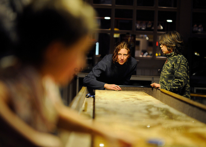 Sherry Dillavou lines up a shuffleboard puck at the Silver Crest Palace in Crestone, CO. Michael Brands for The New York Times.