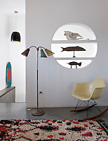 An Eames rocker and a 1950s floor lamp with three lights stand against one wall. A circle with shelves is cut out of the wall allowing a view into the room beyond.