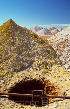 Opal mining 'dumps' or tailings with a descent tunnel in foreground. Coober Pedy, South Australia