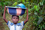 A girl carries dishes in a basin on her head in Mount Barclay, Liberia.