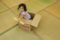 Landscape view of a girl playing in a box inside a temporary community shelter following the 311 Tohoku Tsunami in Ozashi, Japan  © LAN
