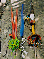 A display of colorful feathers and a native spear against the texture of a tree trunk