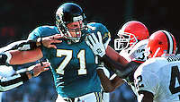 The hands of a referee and Browns player #36 Issac Booth hold back Jacksonville Jaguars rookie offensive tackle #71 Tony Boselli as he expresses a degree of hostility towards Cleveland strong safety #42 Louis Riddick (right) after a third quarter play.