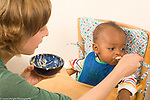 baby boy turning head away to refuse food while being spoon fed