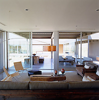 View from the open-plan living area through the sliding glass doors to the covered terraces with dining and seating areas