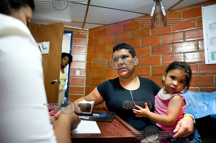 A woman and her daughter attend a health clinic, part the Mission Barrio Adentro project. This aims to offer poor Venezuelans access to health and medical facilities and is funded from oil revenues. The project employs 30, 000 Cuban health professionals: doctors, dentists, physiotherapists and technicians etc.