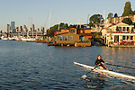 Seattle, Houseboats on Lake Union, woman rower in single racing shell at sunrise passing Westlake docks, Seattle neighborhoods, Washington state, Pacific Northwest, USA, .
