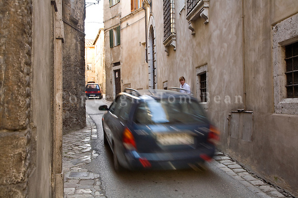 Vehicles drive narrow streets while pedestrian watches traffic among the ancient buildings, in historic town of Amelia, Umbria, Italy, AGPix_1889.