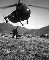An HRS-1 Sikorsky helicopter hovers close to the ground while Marines hook a cargo net loaded with 1,000 pounds of supplies for transportation to the front 12 miles away.  Ca.  1951. M.Sgt. Ed. Waite.  (Marine Corps)<br /> Exact Date Shot Unknown<br /> NARA FILE #:  127-N-A131970<br /> WAR & CONFLICT BOOK #:  1410