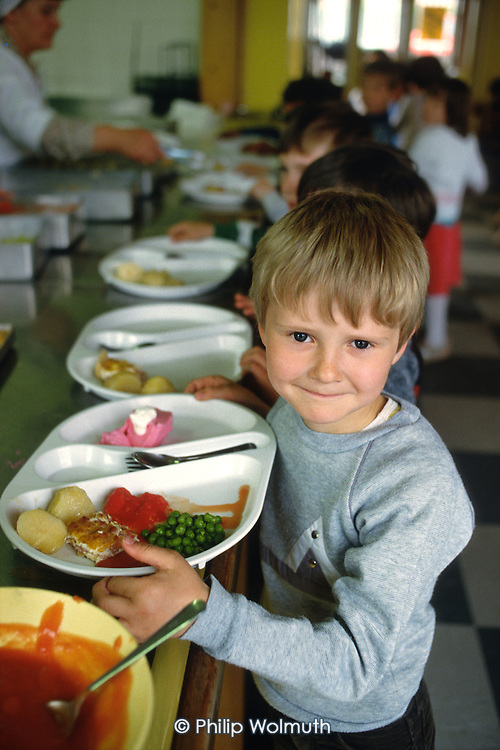 Boy with his lunch of fried fish, potatoes, peas and tomato sauce at a primary school in Buckinghamshire.