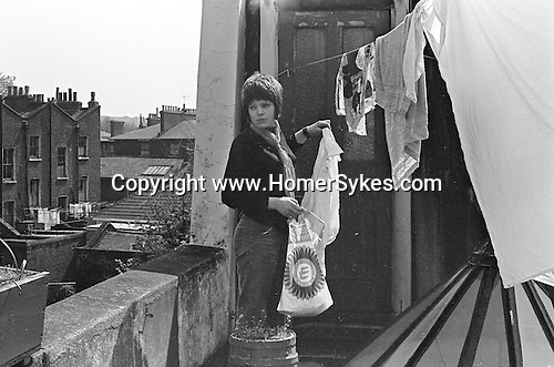 Juliet Watson. Juliet Sykes. Greville Place flat St Johns Wood London 1969 Young woman hanging out washing, bed sitter living.