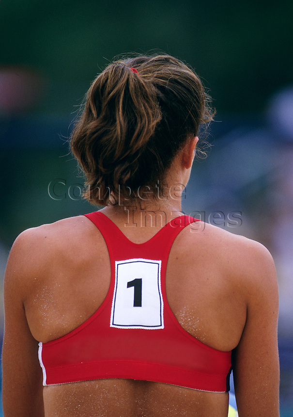 Rear view of a beach volleyball player ready to serve