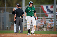 Dartmouth Big Green first baseman Michael Calamari (3) smiles towards his bench as head coach Mike Glavine argues a fair ball call with the home plate umpire during a game against the Northeastern Huskies on March 3, 2018 at North Charlotte Regional Park in Port Charlotte, Florida.  Northeastern defeated Dartmouth 10-8.  (Mike Janes/Four Seam Images)