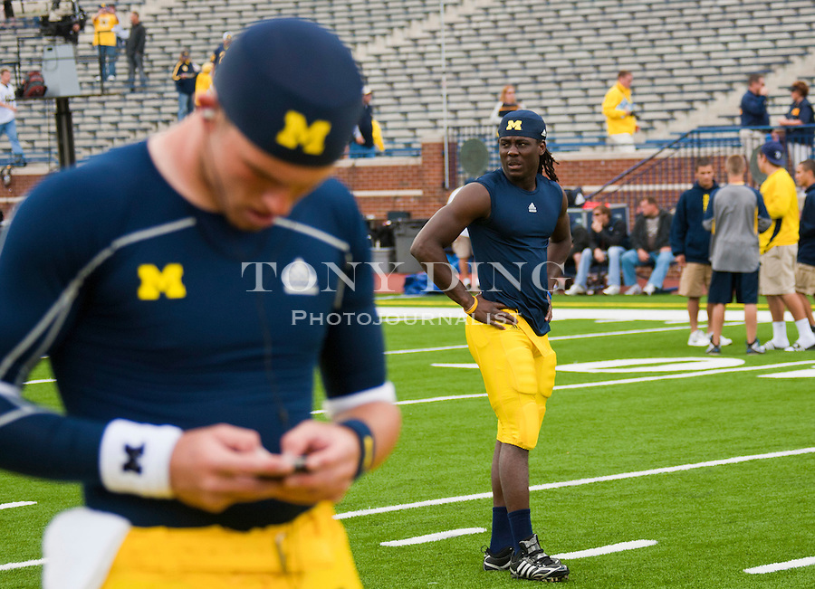 Michigan quarterback Tate Forcier (5) plays with his music player as quarterback Denard Robinson (16) walks the Michigan Stadium field, before an NCAA college football game, Saturday, Sept. 4, 2010, in Ann Arbor, Mich. (AP Photo/Tony Ding)