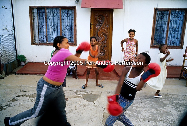 SOWETO, SOUTH AFRICA MAY 3: Children practice boxing outside a house on May 3, 2005 in the Orlando West section of Soweto, Johannesburg, South Africa. Soweto is South Africa?s largest township and it was founded about one hundred years to make housing available for black people south west of downtown Johannesburg. The estimated population is between 2-3 million. Many key events during the Apartheid struggle unfolded here, and the most known is the student uprisings in June 1976, where thousands of students took to the streets to protest after being forced to study the Afrikaans language at school. Soweto today is a mix of old housing and newly constructed townhouses. A new hungry black middle-class is growing steadily. Many residents work in Johannesburg, but the last years many shopping malls have been built, and people are starting to spend their money in Soweto. .(Photo by Per-Anders Pettersson/Getty Images).