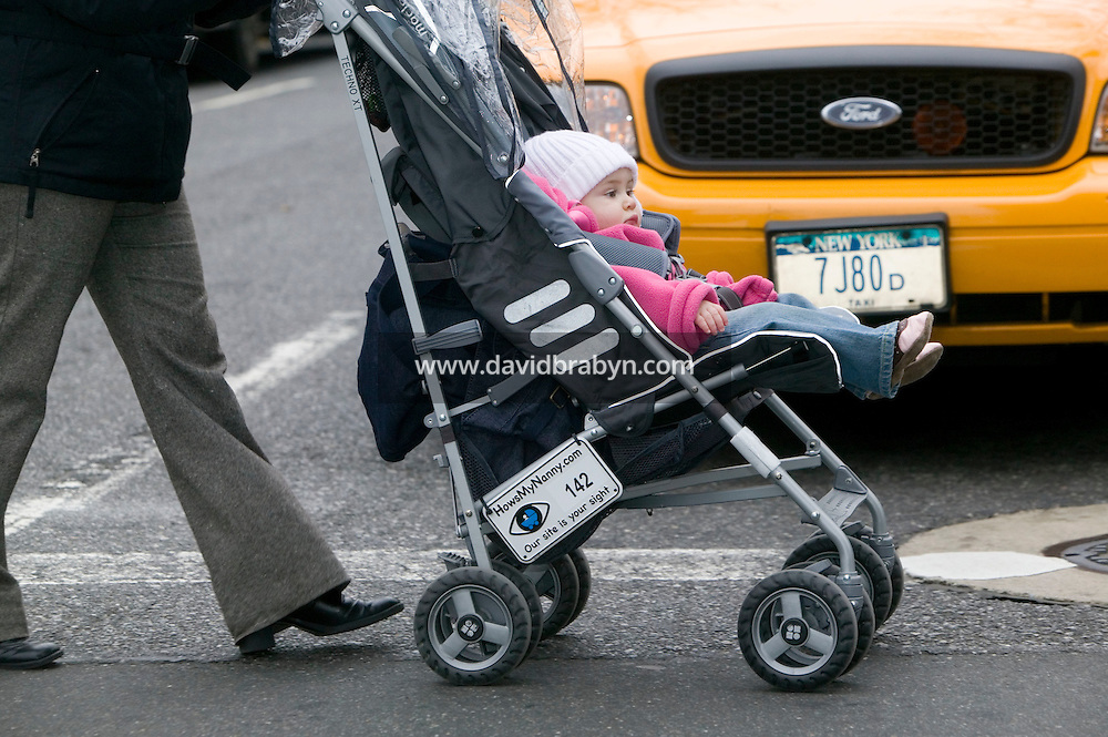 22 November 2006 - New York City, NY - 13 month-old Vivienne Loigman takes a ride in a stroller carrying a Howsmynanny.com number plate in New York City, USA, 22 November 2006. The plate allows people to report good or bad behaviour by the nanny to the website which then relays the information to the parents.