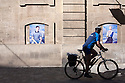 A cuclist along a street looks at some posters of a photo exhibition in Arles, France, July 3, 2016. Tomorrow is the opening day of Les Recontre de la Photograpie. &copy; Carlo Cerchioli<br /> <br /> Un ciclista lungo una strada guarda i manifesti di una mostra di fotografie ad Arles, Francia, 3 luglio 2016. Domani si aprano Les Recontre de la Photograpie