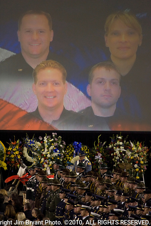 Photos of Lakewood Police officers Greg Richards, upper left, Tina Griswold, upper right, Ronald Owens, lower left, and Sgt. Mark Renninger, lower right, are displayed during a memorial service at the Tacoma Dome on December 8, 2009 in Tacoma, WA. Tina Griswold along with sergeant Mark Renninger, officer Ronald Owens and officer Greg Richards were shot and killed at a coffee shop in the Tacoma suburb of Parkland, November 29 by Maurice Clemmons, who was later shot and killed by police.  Jim Bryant Photo. ©2010. ALL RIGHTS RESERVED.