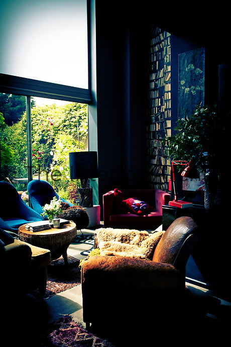 An eclectic deep blue living room with a mix of seating comprising a well worn leather armchair and two retro blue armchairs. The room features a floor to ceiling window, giving a view to the garden.