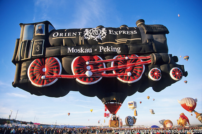 A balloon resembling the engine of the Orient express rises in the morning light at the Albuquerque International Hot Air Balloon Fiesta