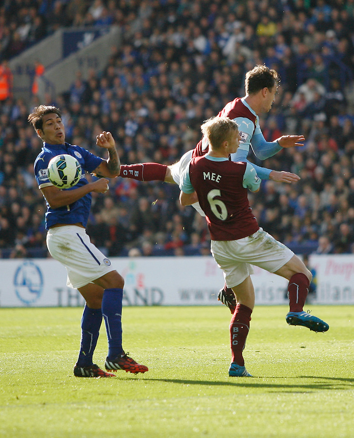 Leicester City's Leonardo Ulloa (L) and Burnley's Ben Mee (C) in action during todays match  <br /> <br /> Photographer Jack Phillips/CameraSport<br /> <br /> Football - Barclays Premiership - Leicester City v Burnley - Saturday 04th October 2014 - King Power Stadium - Leicester<br /> <br /> &copy; CameraSport - 43 Linden Ave. Countesthorpe. Leicester. England. LE8 5PG - Tel: +44 (0) 116 277 4147 - admin@camerasport.com - www.camerasport.com