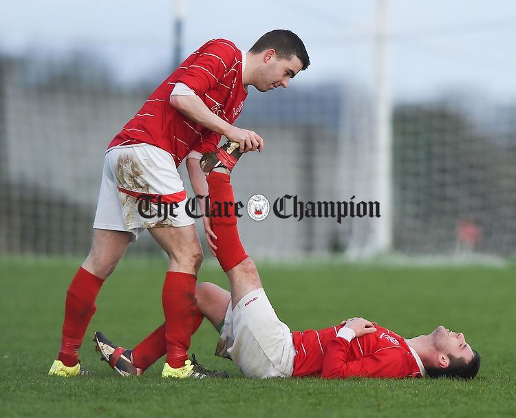 David O Grady of Newmarket Celtic helps team mate Michael Crosby with his ailment  during their Round 6 FAI Junior Cup game in Newmarket. Photograph by John Kelly.