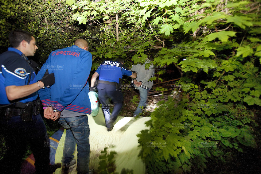 Switzerland. Geneva. Two police officers hold at night two handcuffed men, arrested as squatters, but also illegal migrants, sleeping inside the rooms of a derelict building. Both policemen are wearing a ballistic vest, bulletproof vest or bullet-resistant vest which is an item of personal armor that helps absorb the impact from knives, firearm-fired projectiles and shrapnel from explosions, and is worn on the torso. Soft vests are made from many layers of woven or laminated fibers and can be capable of protecting the wearer from small-caliber handgun and shotgun projectiles, and small fragments from explosives such as hand grenades. 10.05.12 © 2012 Didier Ruef..