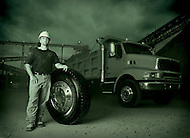 A man wearing a hardhat stands in front of his dump truck with a large tire.