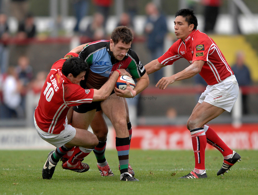 Photo: Richard Lane..Llanelli Scarlets v NEC Harlequins. EDF Anglo-Welsh Cup. 01/10/2006. .Quins' Tom Guest is tackled by Stephen Jones and Regan King (rt).