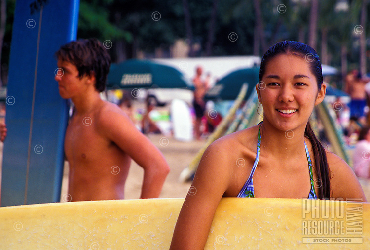 Teen surfers on waikiki beach with boards