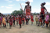 Lolgorian, Kenya. Siria Maasai Manyatta; group of moran doing their traditional 'ipid' jumping dance.